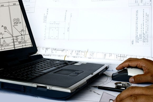 A man working on manufacturing drawings on a laptop.