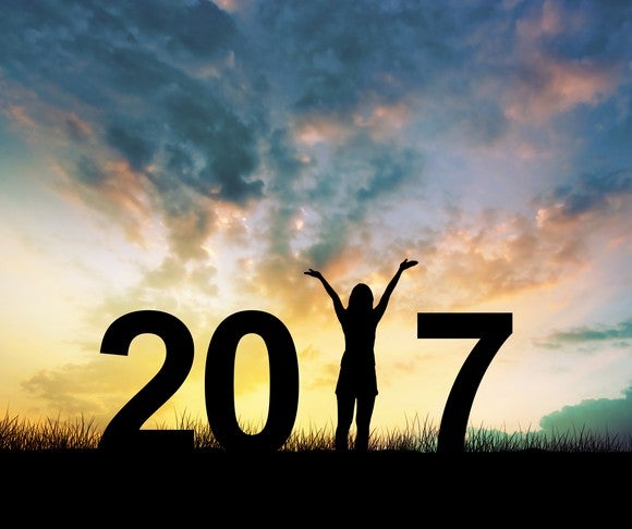 Silhouette of 2017 with woman holding hands up in place of the one