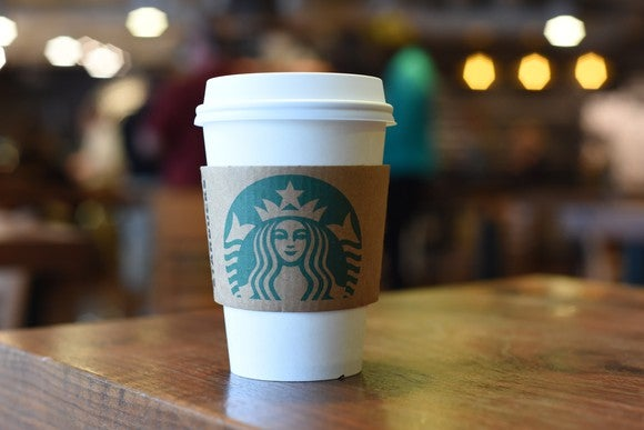 Starbucks beverage with hot cup sleeve sitting on a wooden table with a blurred background