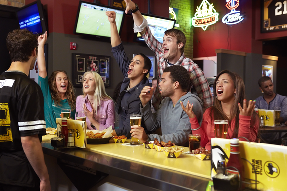 Friends in a Buffalo Wild Wings restaurant, reacting to a sports play on T.V. screens.