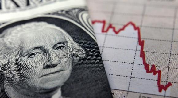Photo of dollar bill next to declining stock chart.