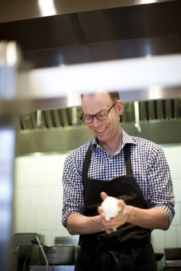 Steve Ells stands in a restaurant kitchen holding an object in his hands