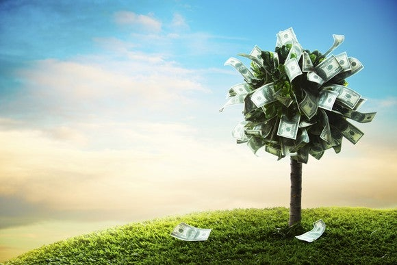 A tree on a hill with dollar bills instead of leaves.