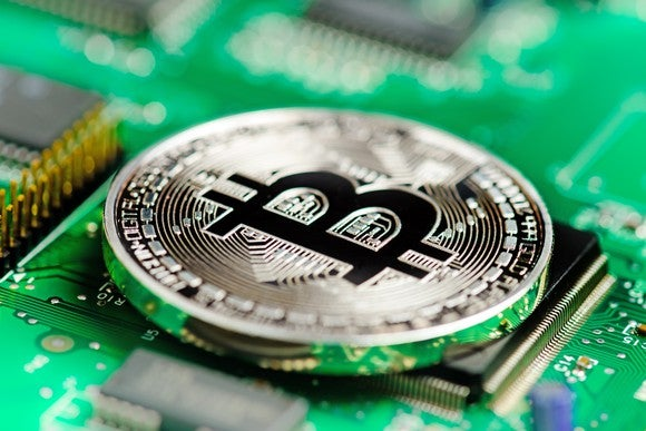A bitcoin sitting on top of a computer board.