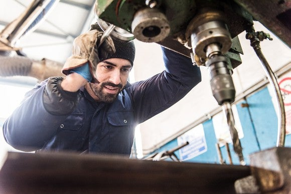 A factory worker at a drill press.