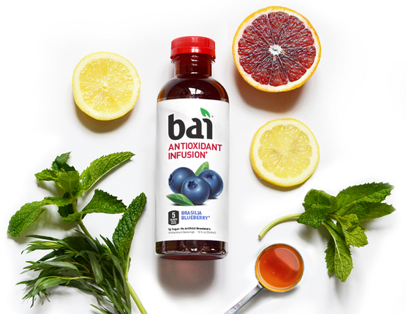A bottle of Bai surrounded by fruits and herbs