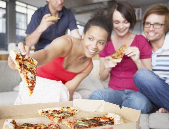 Friends sitting on a couch share a pizza.