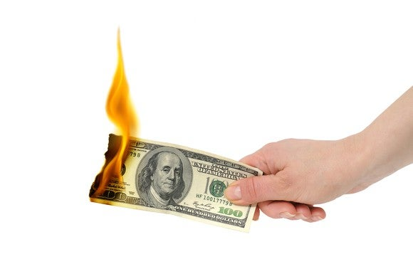 A hand holding a $100 billion that's on fire at the other end.