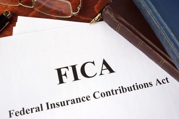Paper saying FICA and what it means, along with glasses and books on a wood desk.