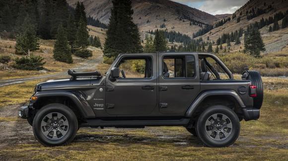 A green 2018 Jeep Wrangler Unlimited Sahara near a mountain road.