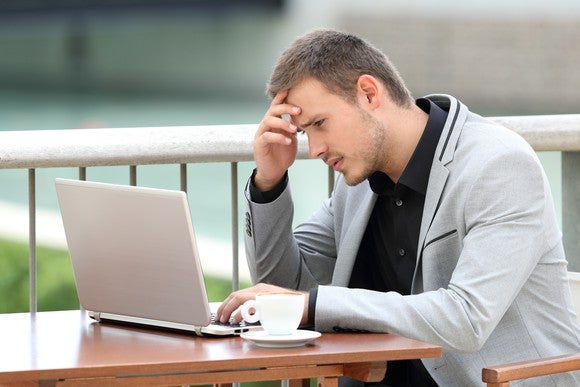 A businessman reading his laptop screen with a confused look on his face.