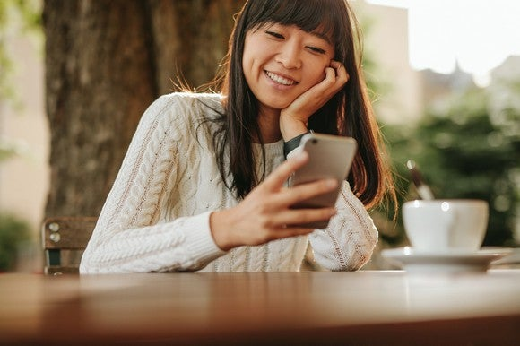 Asian woman smiles at her smartphone.