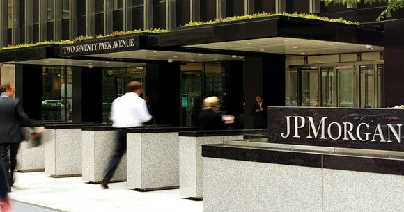 People walking into a building with a JPMorgan sign outside.