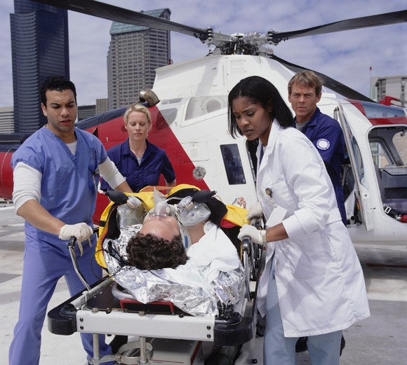 A medical team assists in the transfer of a patient from a medical transport helicopter.