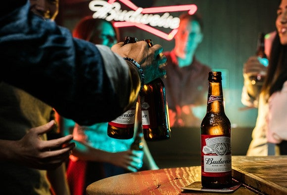 people drinking bottles of Budweiser beer in a bar