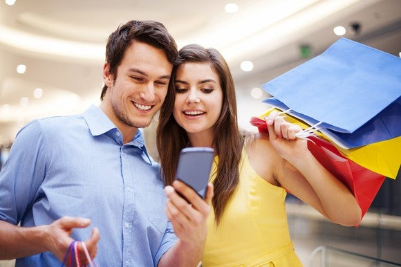 A young couple take a selfie with a smartphone.