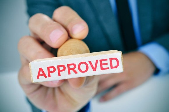 A businessman holds a rubber stamp with the word APPROVED on it.