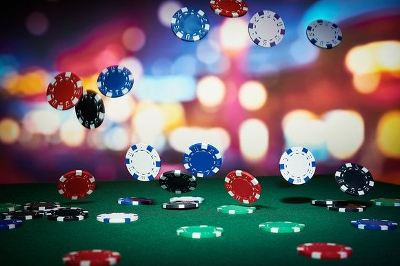 Casino chips falling on a felt table.