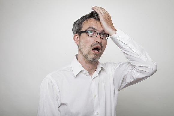 A man with glasses and a white shirt holds his palm to his forehead