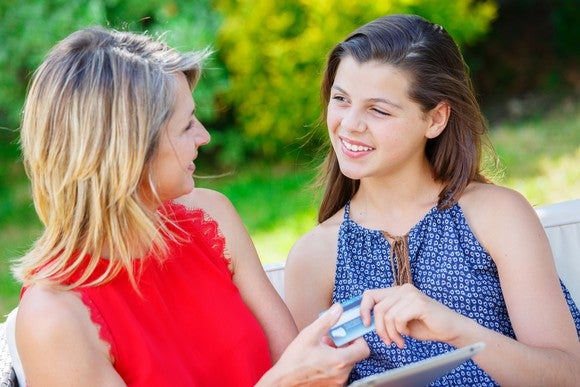 Woman handing teenage girl a credit card