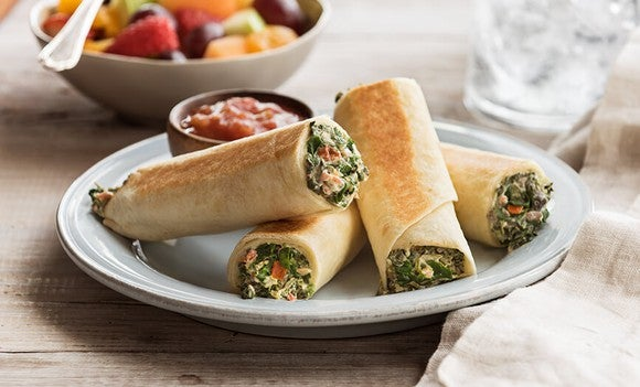 Four spinach roll-ups with dipping sauce in white porcelain bowl.