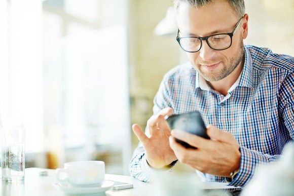 Businessman in dress shirt looking at content on mobile device.