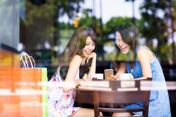 Two young Asian women in a cafe, laughing over mobile device.