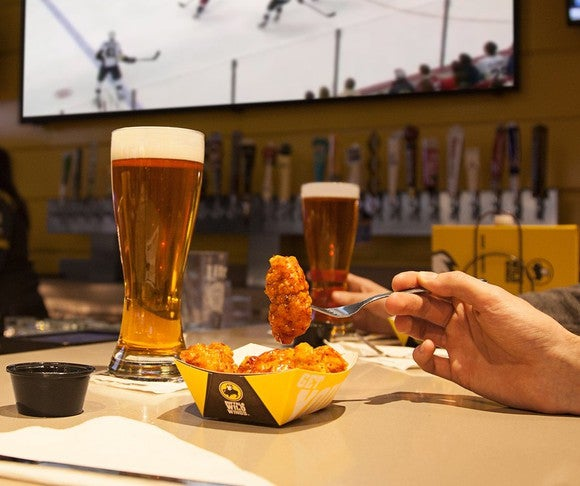 A customer enjoys wings and a beer at Buffalo Wild Wings.