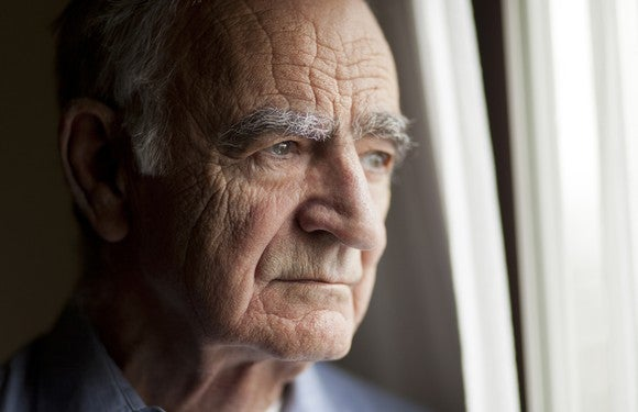 A worried elderly man staring out of a window in his home.