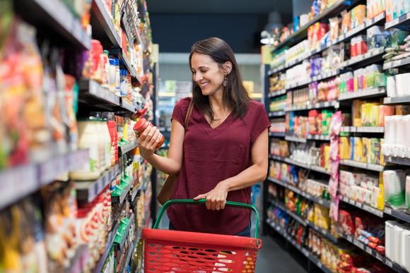 Woman lifting a jar off a supermarket aisle