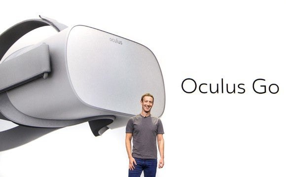 Mark Zuckerberg standing in front of a screen that has a VR headset on it.