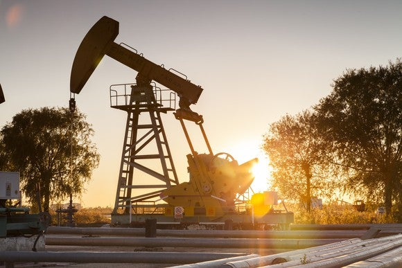 An oil pump with pipes in the foreground and the sun setting behind it.