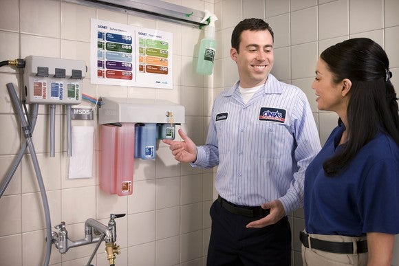 Cintas employee showing a wall mounted cleaning supply dispenser.