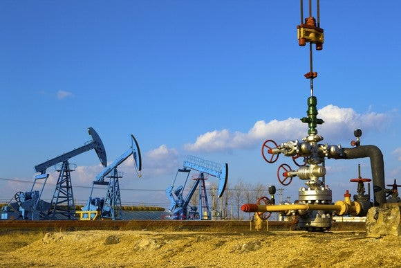 A wellhead with oil pump jacks in the background.