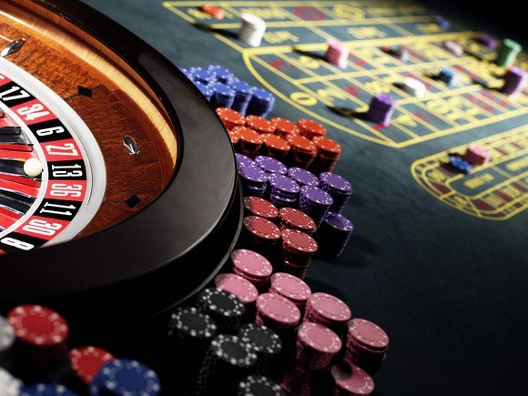 A roulette table with chips stacked around the wheel.