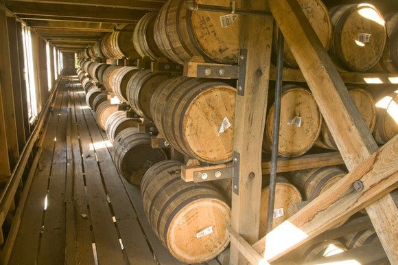 A line of whiskey barrels stacked on three shelves