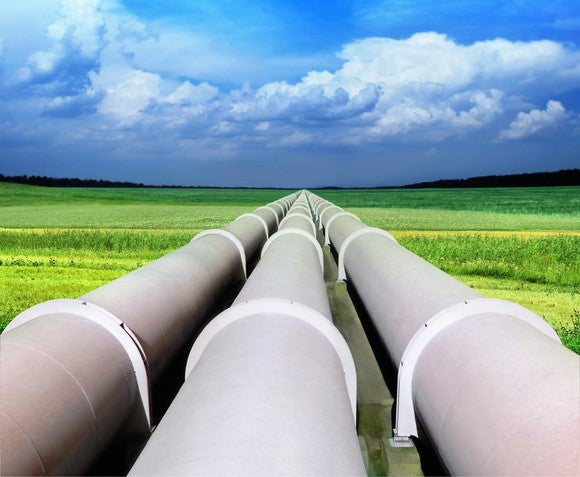 Pipelines on green grass heading towards the blue sky.