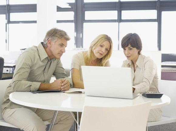 Couple with financial advisor looking at laptop