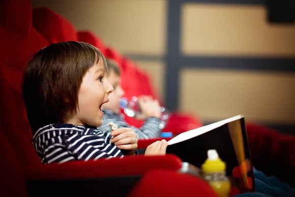 Two children, eating popcorn and watching a movie at the theater.