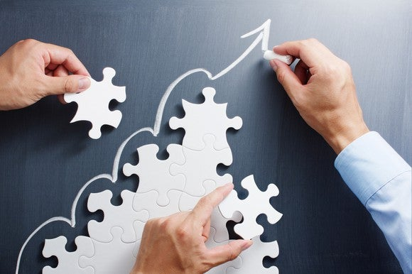three hands assembling white jigsaw puzzle pieces in shape of pyramid with arrow drawn going upward