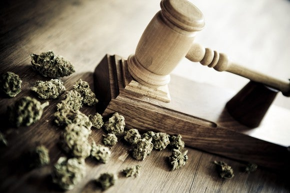 Cannabis buds on a judge's bench next to a gavel.
