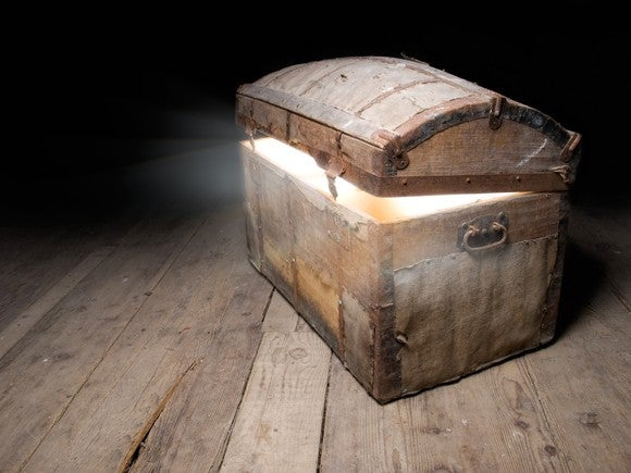 A slightly opened treasure chest sitting on an old floor.