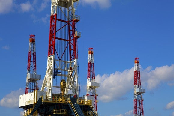 drilling rigs with a blue sky backdrop.