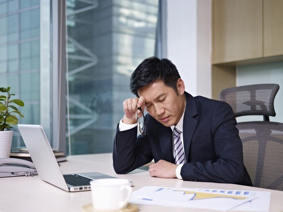 A businessman in front of a computer thinking hard