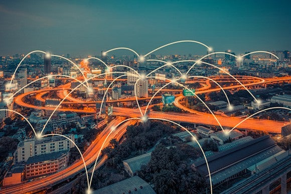 A city's cloverleaf highway lit up in early evening with multiple connected points.