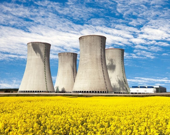 Several nuclear reactors against a yellow field and blue sky backdrop.