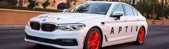 A white BMW sedan with Aptiv logos.
