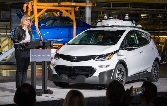 Barra is shown standing next to a white Chevrolet Bolt EV with visible self-driving hardware while speaking at GM's factory in Orion Township, Michigan.