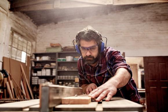 A carpenter cutting wood in his workshop