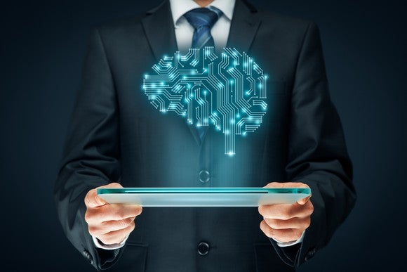 A man in a suit from the neck down holds a tablet and a blue cartoon brain sits above it like a hologram.